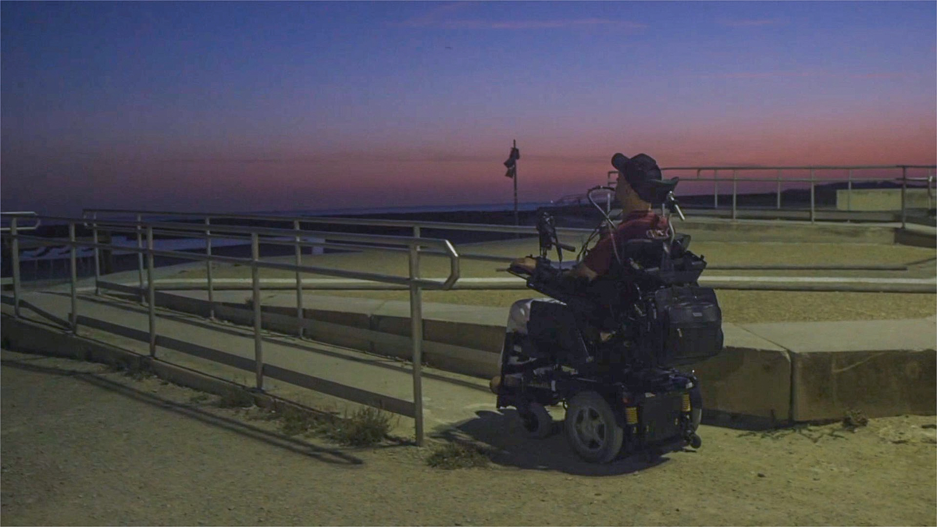 Patrice en fauteuil sur une ongue rampe menant à la plage au coucher de soleil
