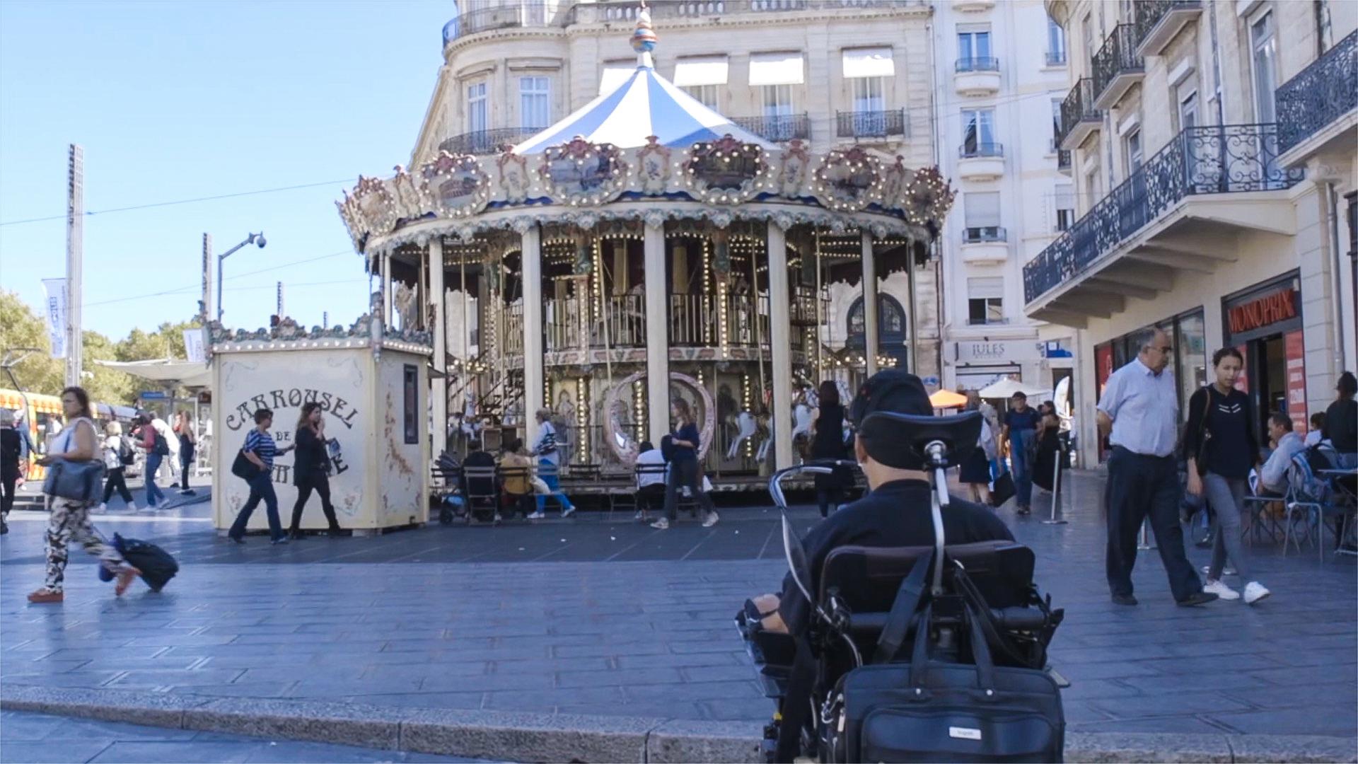 Patrice devant le Carrousel au Centre de l'immense Place de la Comédie