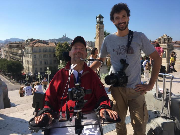 Patrice Lamarche et son accompagnateur Jean-Sébastien en grand plan devant une vieille ville