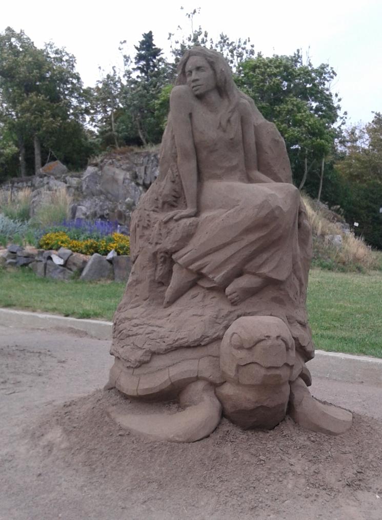 Sculpture de sable d'une femme sur une tortue